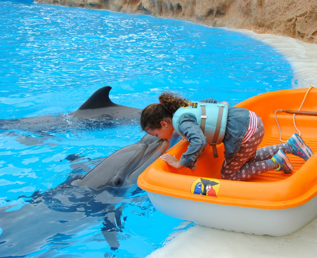 Isabelle kissing a dolphin